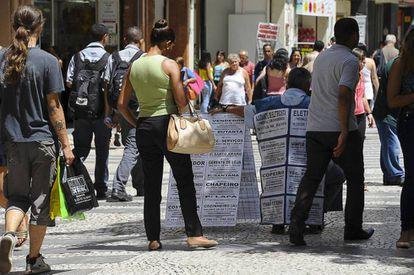 A black woman looks at job advertisements in a São Paulo street.