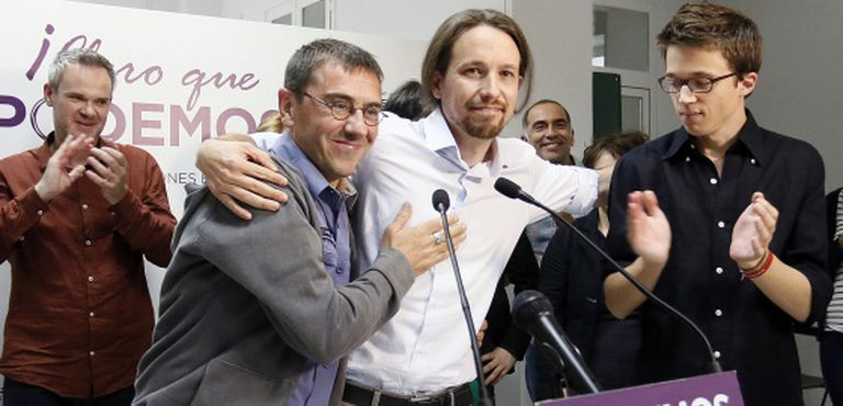 Pablo Iglesias (center) embraces party co-founder Juan Carlos Monedero after learning the results of the European elections in Spain.