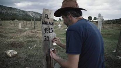 Association founder Sergio García paints the fictitious grave marker for Eli Wallach.