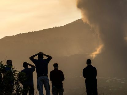 Residents look from a hill as lava continues to flow from the volcano on the island of La Palma.
