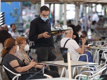 A waiter serves customers at a sidewalk café in L'Hospitalet, Barcelona.