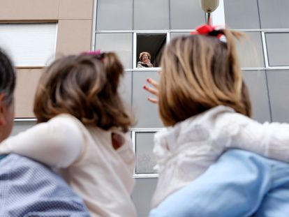 A grandmother waves to her granchildren from her home in Spain's Canary Islands.
