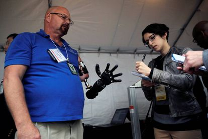 A man demonstrates his robotics arm at the DARPA open day.