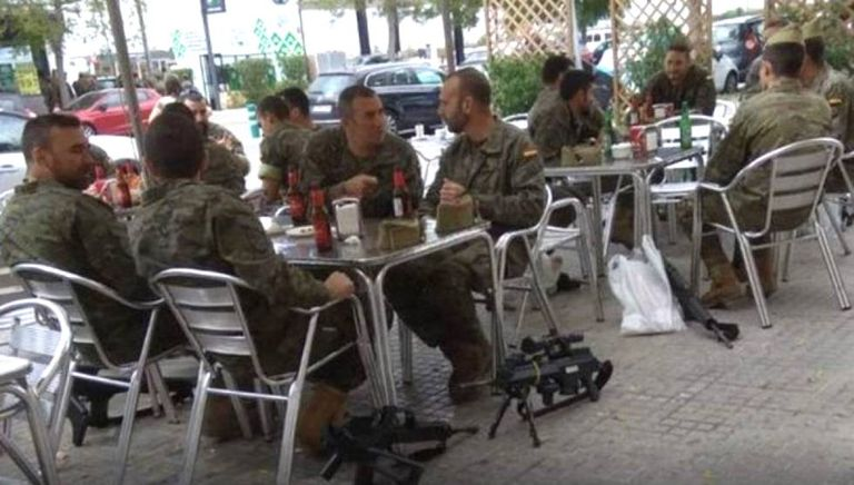 The soldiers drinking beer with their weapons on the floor in Vilafranca del Penedès (Barcelona).