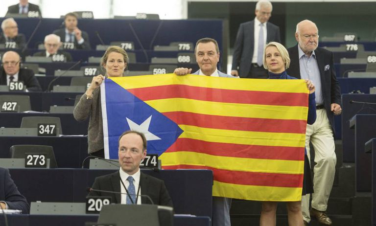 Members of the European Parliament pose with a Catalan secessionist flag during the debate