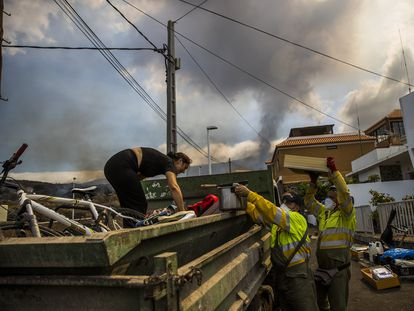 Residents of Todoque, assisted by municipal employees, load their belongings onto a truck.
