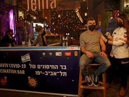 A health worker administers a Covid vaccine in a bar in Tel Aviv.