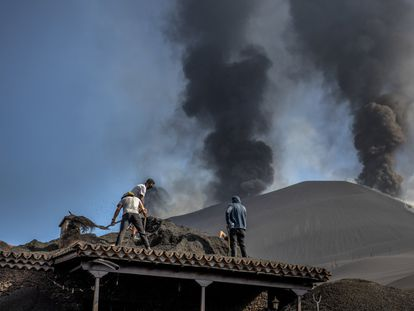 Residents shoveling volcanic ash from the roof of a home in Las Manchas, on the island of La Palma.