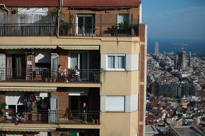 The residents of an apartment block in Barcelona sit out on their balconies during quarantine.