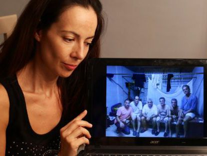 The wife of José Mocholí, Eva Báguena, shows a photo of her husband and his five colleagues.