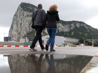 Two people cross the airport of Gibraltar.