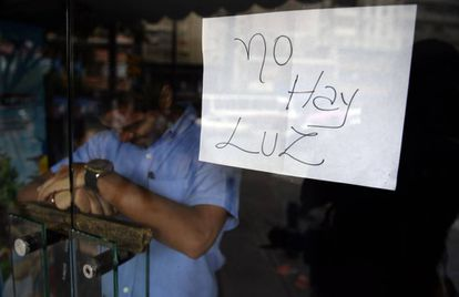 """No electricity"" reads a sign in a closed shop in Caracas."