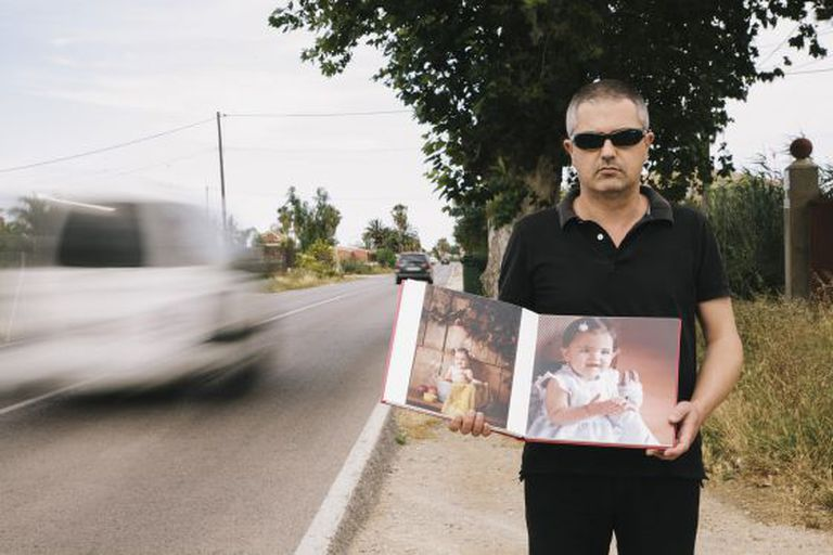 Antonio Ángel Pertusa holds pictures of his daughter Julia near the scene of the accident.