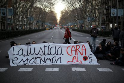 """Protesters on Barcelona's Gran Vía hold a banner with the message """"Spanish justice, Cara al Sol"""" in reference to the anthem of fascist-inspired party Falange."""