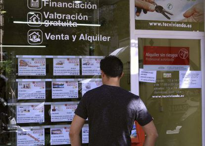 A man checks out house listings at a realtor in Madrid.