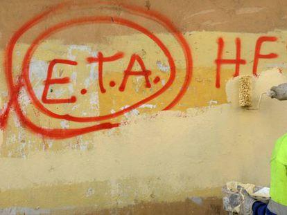 A municipal worker cleaning up graffiti in Guernica.