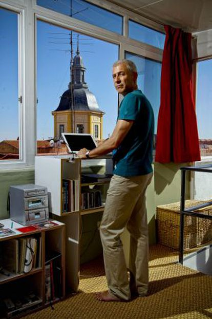 José Ovejero standing at his computer at his home in Madrid.