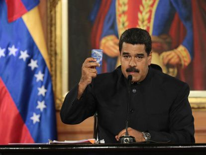 Maduro holds a copy of the Venezuelan Constitution during a speech.