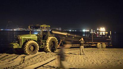 A tractor hauls a drug boat on Playa de Palmones.