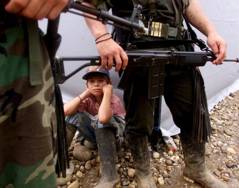 A boy sits among a group of FARC guerrillas in San Vicente del Caguán, in 2000.