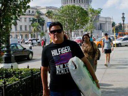 A man wearing an imported US designer t-shirt walks in Havana.