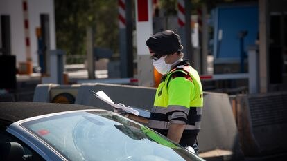 A Catalan regional police officer asks a driver to justify his trip at a toll plaza in La Roca del Vallès on Thursday, at the start of the Easter holiday.  09/04/2020