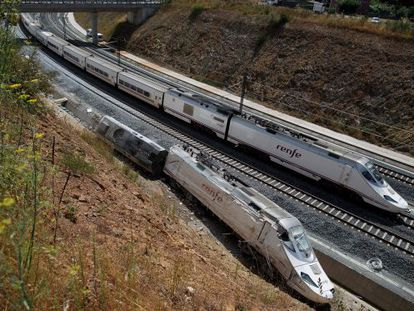 An Alvia train passes the wreckage of the Santiago crash.