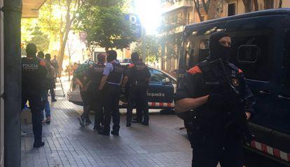 Police escort a suspect on Tamarit street in Barcelona.