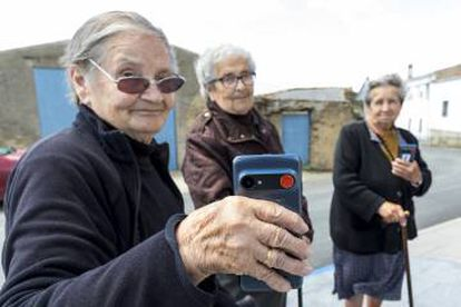Three residents show the mobile device with the red emergency button.