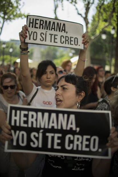 """Protesters in Seville hold up signs reading """"Sister, I believe you."""""""