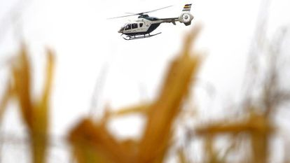 A police helicopter flies over the countryside around El Salobral.