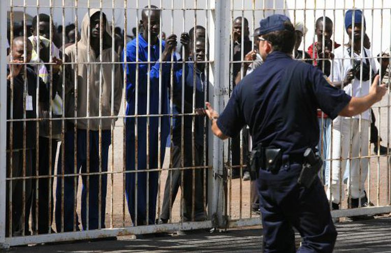 A policeman with immigrants in an internment center in the Canary Islands.