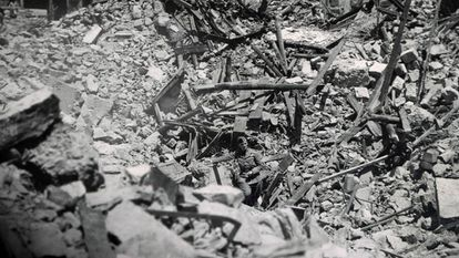 Nazi soldier studies wreckage from bomb attack on four Spanish villages.