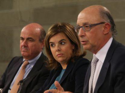 Economy Minister Luis de Guindos, Deputy PM Soraya Sáenz de Santamaría and Finance Minister Cristóbal Montoro speak to the press on Friday.