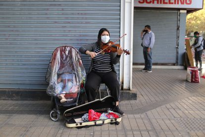 A woman plays violin beside her child in Santiago, the capital of Chile.