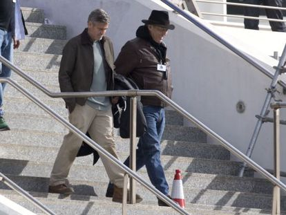 George Clooney (l) walks down the stairs of Valencia's Science Museum where his is shooting 'Tomorrowland.'