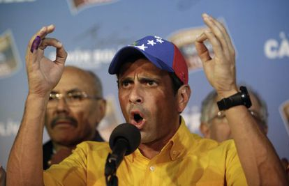 Opposition presidential candidate Henrique Capriles talks to journalists after official results of the elections were announced in Caracas.