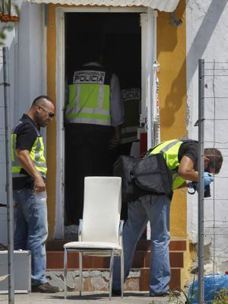 Forensic police examine the home where a seven-year-old was killed in Seville's Tres Mil Viviendas neighborhood.