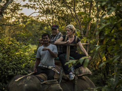 Veterinarian Deborah McCauley and Bishnu Lama on an elephant in Chitwan.