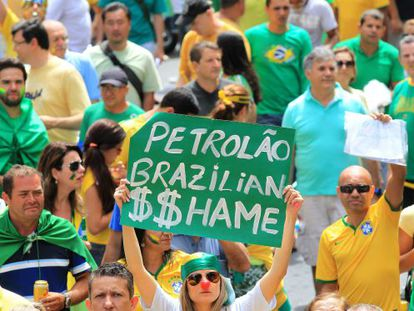 "A woman holds up a sign reading ""Brazilian Oil $$hame"" during Sunday's protests held against Rousseff's policies."