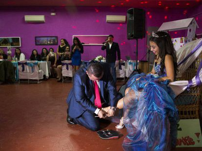 Bernardo Zapata helps his daughter Aleja into high-heeled sandals at her quinceañera party in Madrid.