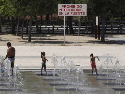 A group of people cool off in the fountains of Juan Carlos I Park in Madrid.