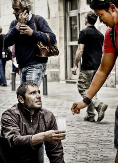 A passer-by gives a coin to a homeless man on the streets of Madrid.