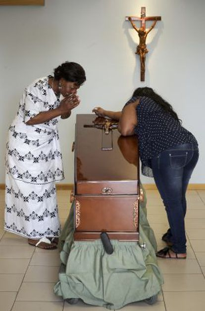 The mother of Samba, Clementine Nijba (l), weeps next to the coffin of her daughter.