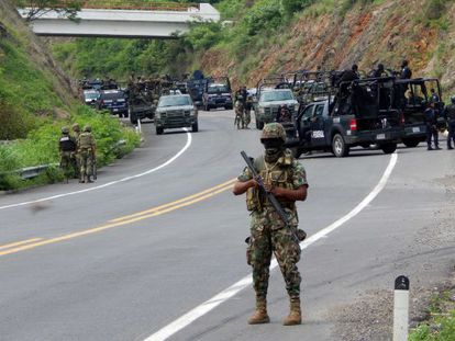 Soliders stand guard on a highway near the town of Arteaga, Michoacán state, where 22 killings were reported Tuesday.
