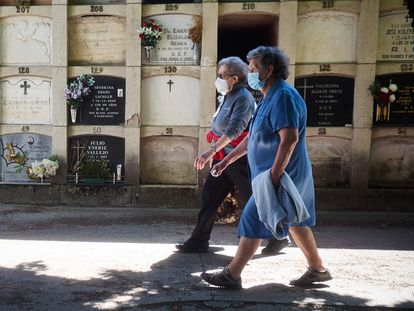 Two seniors wearing masks make a visit to a cemetery in Pamplona, northern Spain.