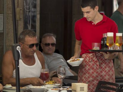 A waiter serves customers in a bar in Ronda, Andalusia.