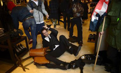 A security guard topples over as demonstrators invade a branch of Zara in Barcelona on Wednesday.