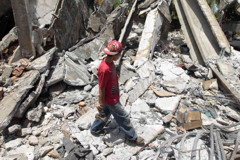 A boy inspects ruins from a building that collapsed in 1972 and was damaged again by last week's quake.