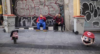 Marcos Herrera, dressed as Mario, and Ronald, dressed as Freddy Krueger, take a break.